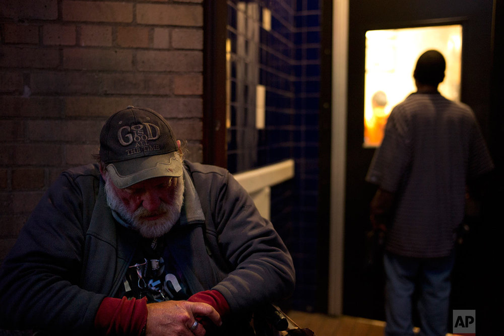 "Charles, a 59-year-old homeless man who only gave his first name, wears a hat that says ""God is good all the time"" as he and other homeless people wait to enter Seattle's Union Gospel Mission to spend the night at the shelter Wednesday, Sept. 27, 2017, in Seattle. (AP Photo/Jae C. Hong)"