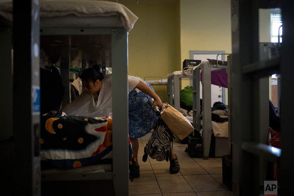 Stella Tatola, a homeless woman staying in a women's shelter at the Sanctuary, cleans her bed while getting ready to start her day, Tuesday, Oct. 24, 2017, in San Francisco. (AP Photo/Jae C. Hong)
