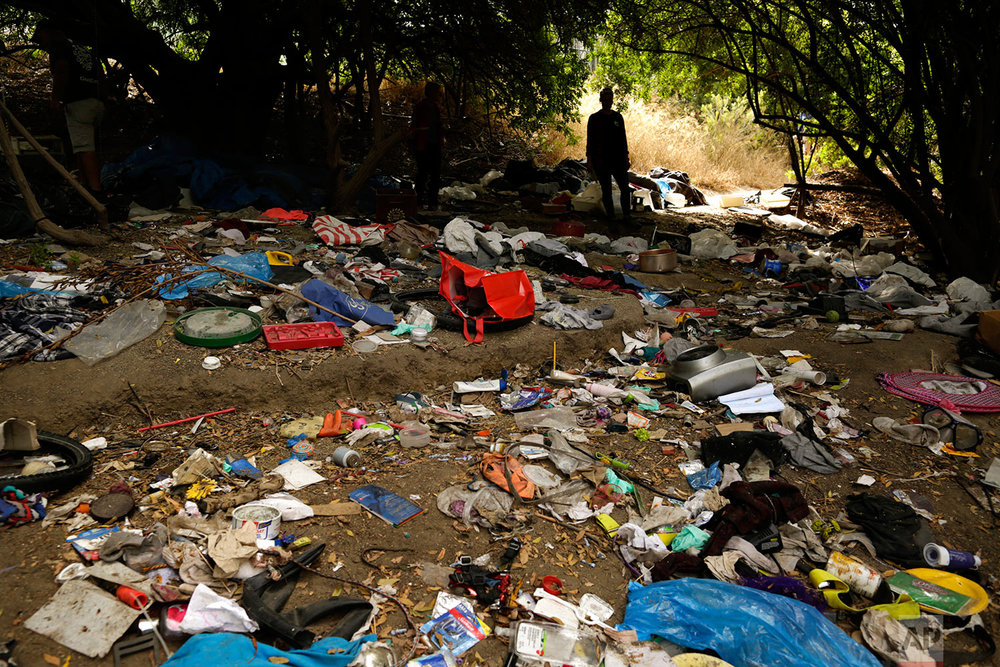 A woman looks over trash from an encampment for homeless people along the San Diego River in San Diego on Sept. 22, 2017. California declared a statewide emergency due to a hepatitis A outbreak linked to homeless encampments. Comparisons are being made to conditions more commonly seen in Third World countries. (AP Photo/Gregory Bull)