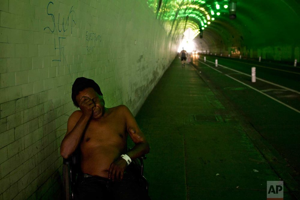 James Williams, 50, who has been on the street for 20 years, sits in a wheelchair in the tunnel where he spends the night Friday, Sept. 1, 2017, in downtown Los Angeles. Williams was dropped off by a taxi near the tunnel the night before, after being hospitalized for more than a week due to respiratory problems. He wanted to avoid a shelter because he said it would be too crowded. (AP Photo/Jae C. Hong)