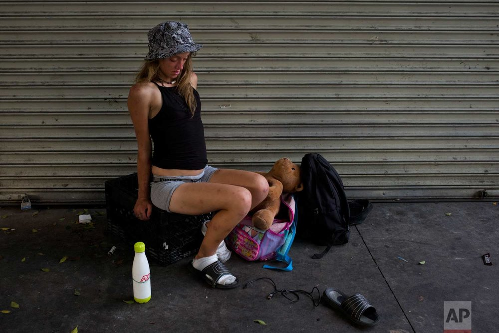 A young homeless woman, in a drug-induced state, wobbles while sitting on a milk case with a teddy bear in Los Angeles' Skid Row area, home to the nation's largest concentration of homeless people, on Friday, Sept. 1, 2017. The latest nationwide homeless count shows that 4 of every 10 people living on the street are severely mentally ill or have a serious drug addiction. (AP Photo/Jae C. Hong)