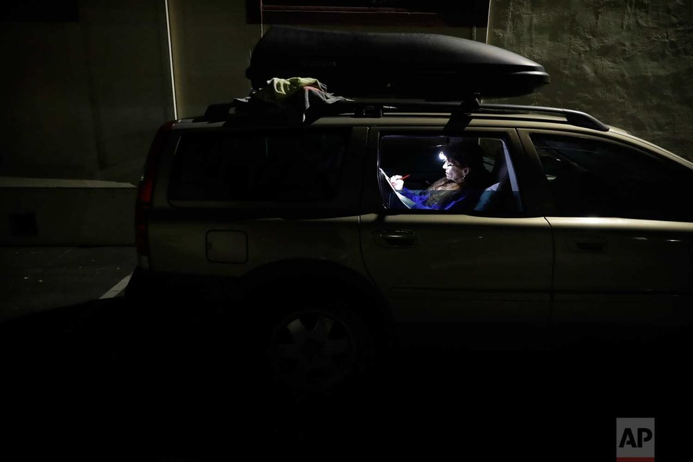 Ellen James-Penney, a lecturer at San Jose State University, prepares a lesson for the class she teaches, inside a station wagon where she sleeps at Grace Baptist Church on Tuesday, Oct. 10, 2017, in San Jose, Calif. Unable to afford rent in the Silicon Valley on her adjunct professor wages, James-Penney, her husband and two dogs, are forced to live in their car. A homeless crisis of unprecedented proportions is rocking the West Coast, and its victims are being left behind by the very things that mark the region's success: soaring housing costs, rock-bottom vacancy rates and a roaring economy that waits for no one. (AP Photo/Marcio Jose Sanchez)