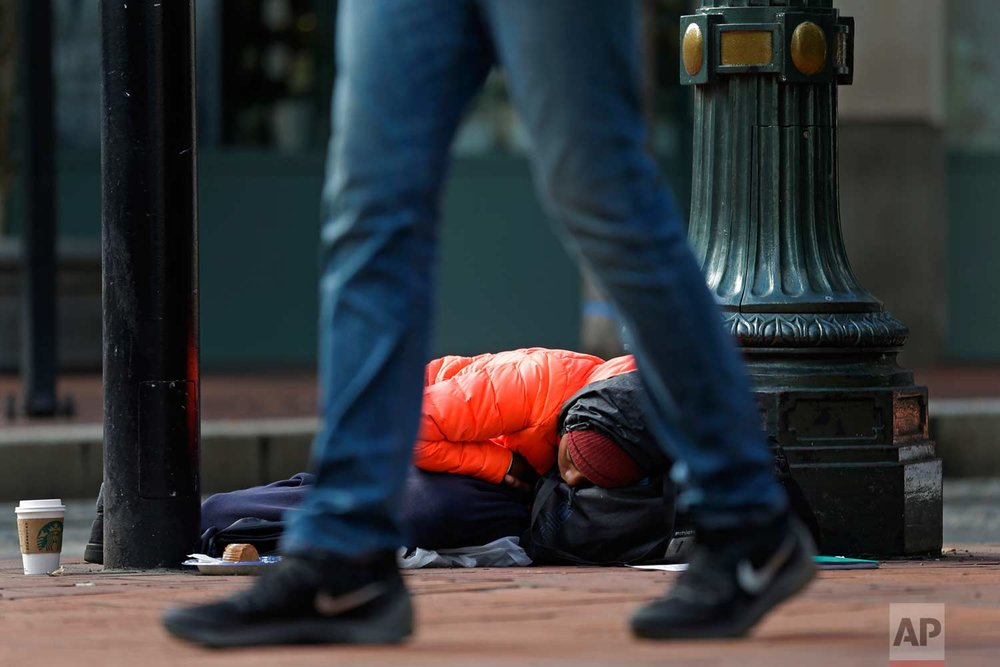 "Cheyvonne Price, who says she is homeless primarily due to heroin addiction, naps on a sidewalk outside a Starbucks in downtown Portland, Ore., on Sept. 20, 2017, after spending a night outside on the streets trying to keep dry in the rain. Price said she hoped to get enough money during the day to afford a bed at a hostel for the night and said that she wishes people would realize that the homeless ""are not all bad people."" (AP Photo/Ted S. Warren)"