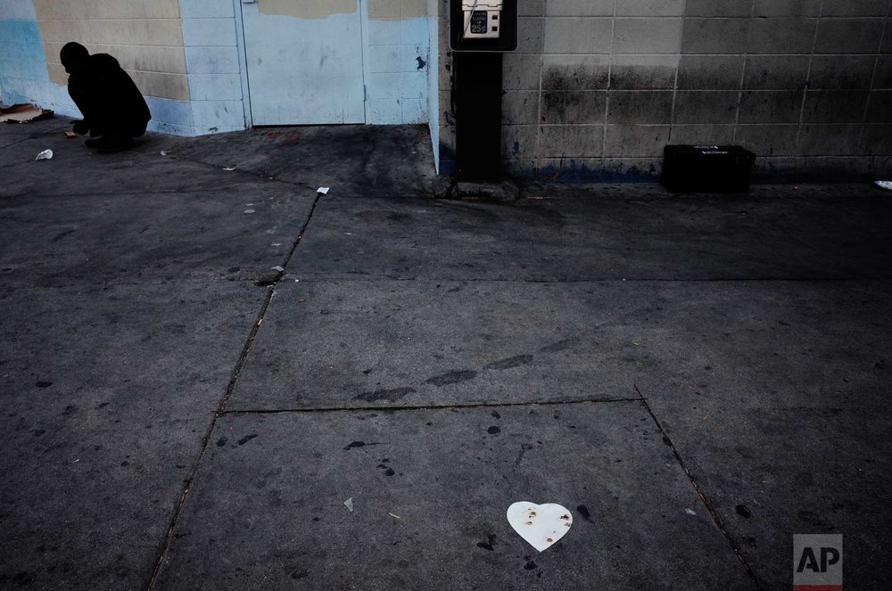 Crouching against the wall near a heart-shaped cutout, a mentally-disabled homeless man mumbles to himself on a sidewalk stained with urine Thursday, Aug. 31, 2017, in downtown Los Angeles. The latest nationwide homeless count shows that 4 of every 10 people living on the street are severely mentally ill or have a serious drug addiction. (AP Photo/Jae C. Hong)