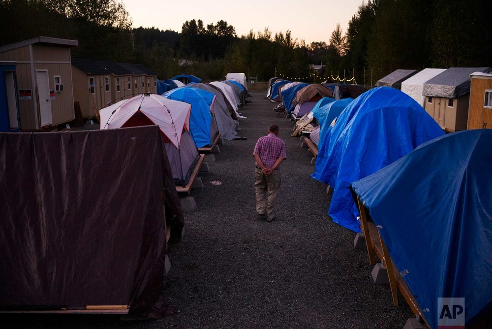 "Seattle native Robert Irwin, 72, who has been homeless for seven months, walks between rows of tents at Camp Second Chance, a city-sanctioned homeless encampment, Tuesday, Sept. 26, 2017, in Seattle. Irwin said he is planning a trip to Michigan to see his older sister. ""I have my own SUV, Chevy Trailblazer. I want to go in March. It will be my last trip."" (AP Photo/Jae C. Hong)"