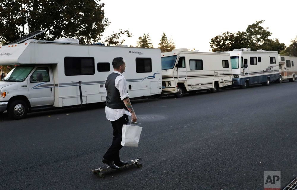 In this photo taken Oct. 5, 2017, a man skates past a row of RVs where people live and sleep in the heart of silicon valley in Mountain View, Calif. Apartments across the street start at over $3,000 a month. (AP Photo/Marcio Jose Sanchez)