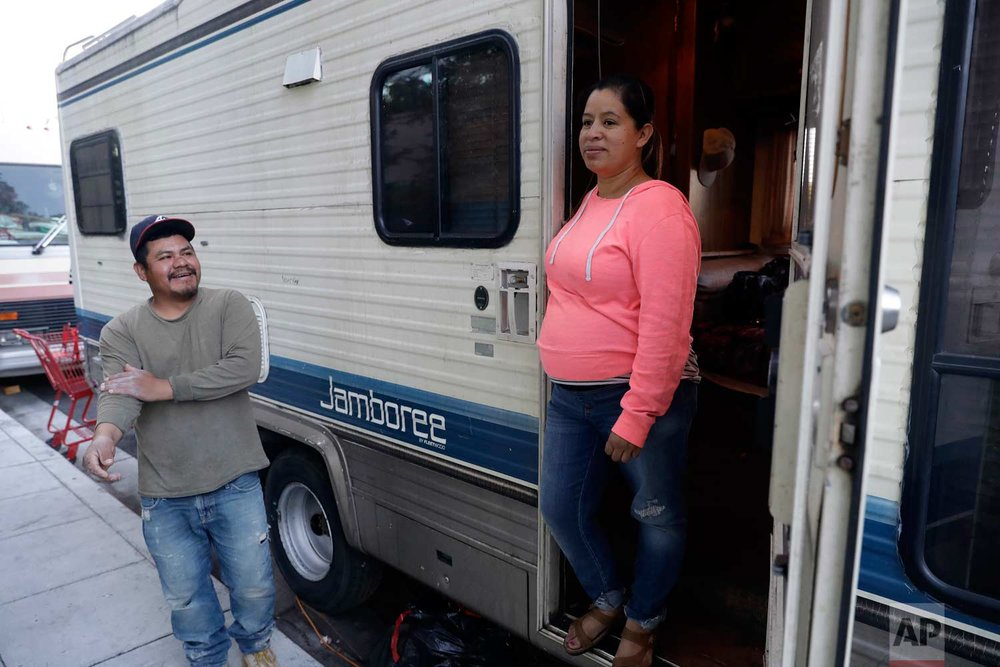 Delmi Ruiz, right, and her husband Benito Hernandez chat outside their RV where their family lives and sleeps on Thursday, Oct. 5, 2017, in Mountain View, Calif. The Ruiz Hernandez was family was left homeless after the landlord in the apartment they rented hiked their rent beyond what they could afford. A homeless crisis of unprecedented proportions is rocking the West Coast, and its victims are being left behind by the very things that mark the region's success: soaring housing costs, rock-bottom vacancy rates and a roaring economy that waits for no one. (AP Photo/Marcio Jose Sanchez)