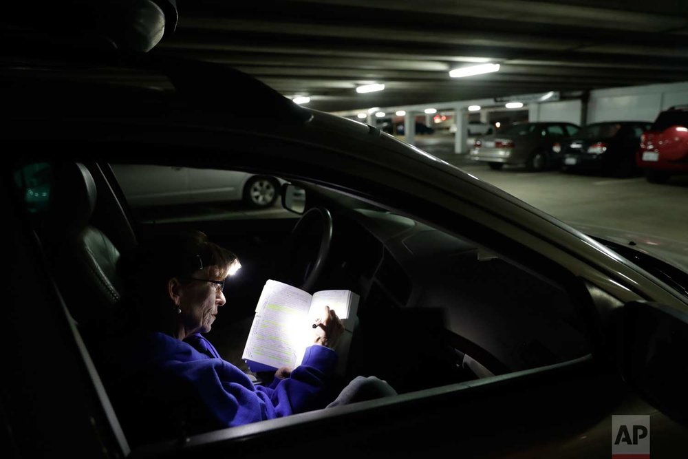 Ellen Tara James-Penney, a lecturer at San Jose State University, prepares her lesson plan inside the station wagon where she sleeps on Tuesday, Oct. 10, 2017, in San Jose, Calif. (AP Photo/Marcio Jose Sanchez)