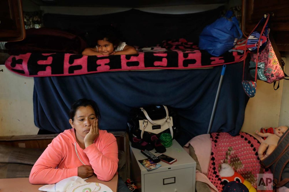 In this photo taken Oct. 5, 2017, Delmi Ruiz, bottom, sits inside an RV where her family lives and sleeps under her daughter Delmi, 4, top, in Mountain View, Calif. The Ruiz Hernandez family was left homeless after the landlord in the apartment they rented hiked their rent beyond what they could afford. (AP Photo/Marcio Jose Sanchez)