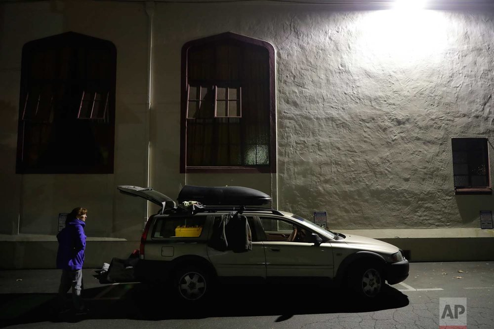 In this photo taken Oct. 10, 2017, Ellen Tara James-Penney, a lecturer at San Jose State University, prepares to stay the night inside her station wagon in the parking lot of Grace Baptist Church in San Jose, Calif. (AP Photo/Marcio Jose Sanchez)