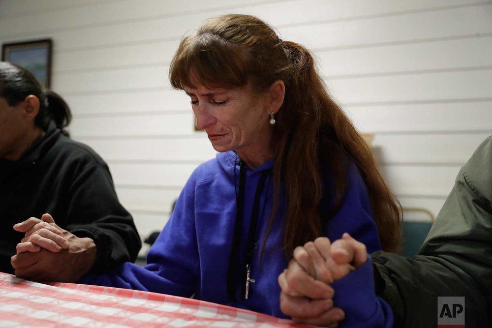 Ellen Tara James-Penney, a lecturer at San Jose State University, prays before receiving a meal at Grace Baptist Church on Tuesday, Oct. 10, 2017, in San Jose, Calif. (AP Photo/Marcio Jose Sanchez)