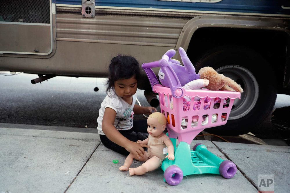 Delmi Ruiz Hernandez, 4, top, plays outside of an RV where her family lives on Thursday, Oct. 5, 2017, in Mountain View, Calif. The Ruiz Hernandez was family was left homeless after the landlord in the apartment they rented hiked their rent beyond what they could afford. (AP Photo/Marcio Jose Sanchez)