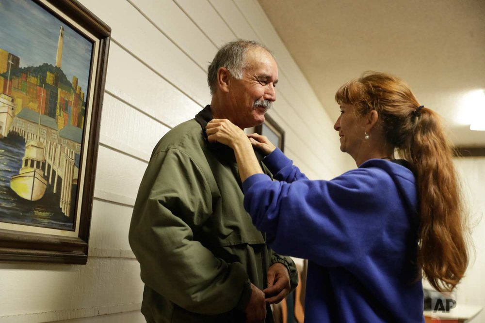 Ellen Tara James-Penney , a lecturer at San Jose State University, right, fixes the collar on her husband Jim's jacket at Grace Baptist Church on Tuesday, Oct. 10, 2017, in San Jose, Calif. (AP Photo/Marcio Jose Sanchez)