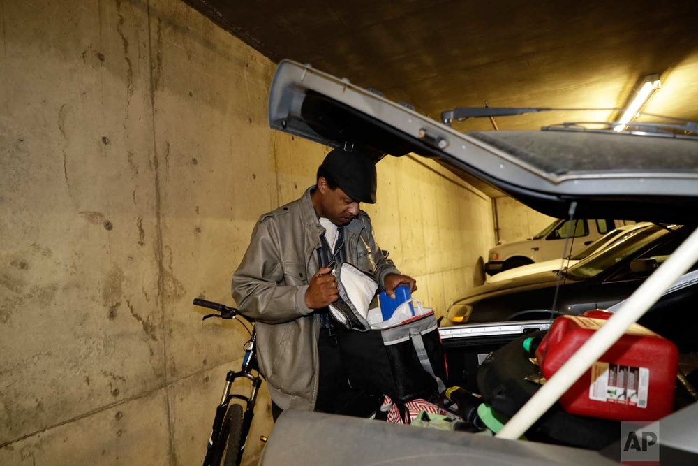 In this photo taken Oct. 25, 2017, Albert Brown III, who works as a security officer, goes through the trunk of his car in San Carlos, Calif. (AP Photo/Marcio Jose Sanchez)