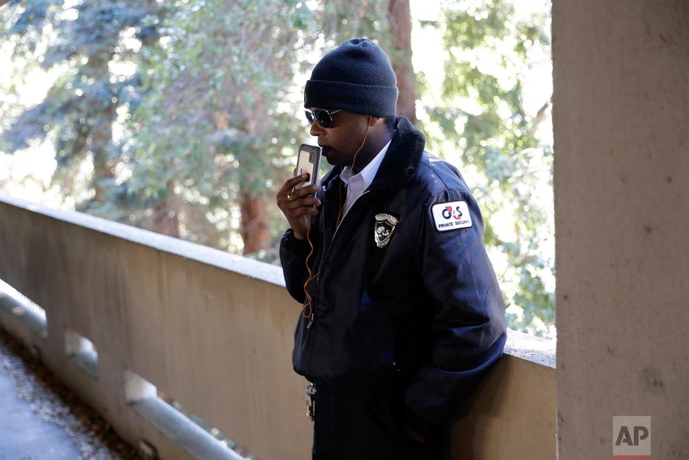 In this photo taken Oct. 26, 2017, Albert Brown III, who works as a security officer, talks to a friend after the end of his shift in San Carlos, Calif. (AP Photo/Marcio Jose Sanchez)