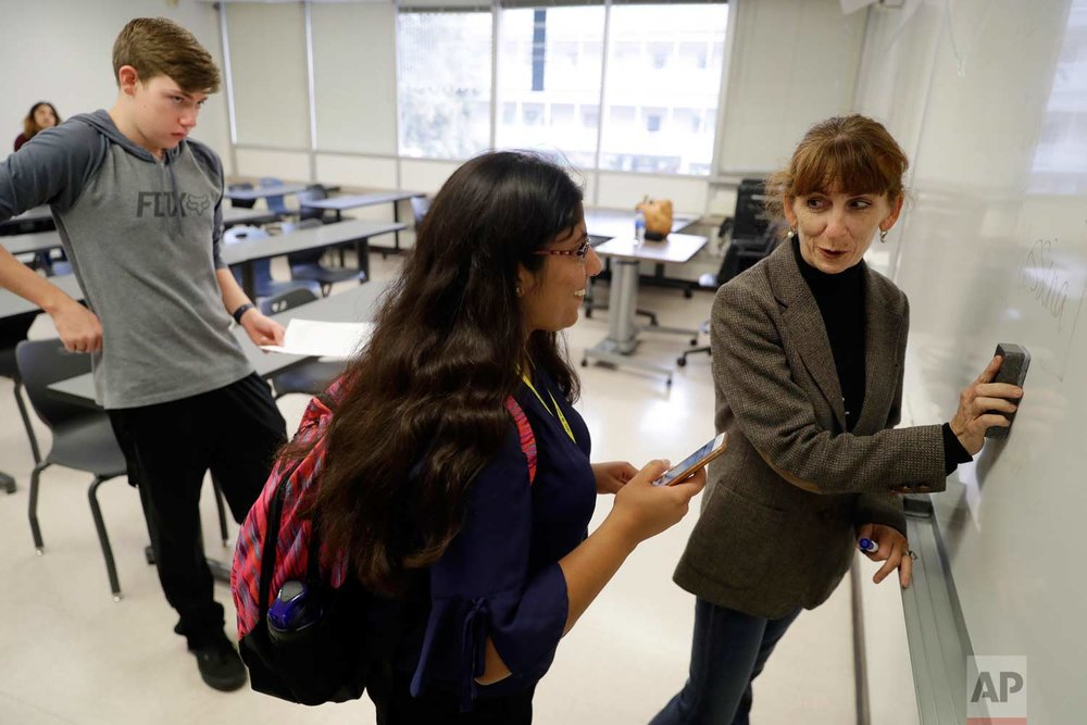In this photo taken Oct. 11, 2017, Ellen Tara James-Penney, right, a lecturer at San Jose State University, talks with a student at the end of her English class on the university's campus in San Jose, Calif. (AP Photo/Marcio Jose Sanchez)