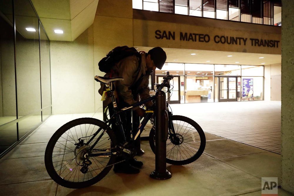 In this photo taken Oct. 25, 2017, Albert Brown III, who works as a security officer, locks his bike in front of his workplace in San Carlos, Calif. (AP Photo/Marcio Jose Sanchez)