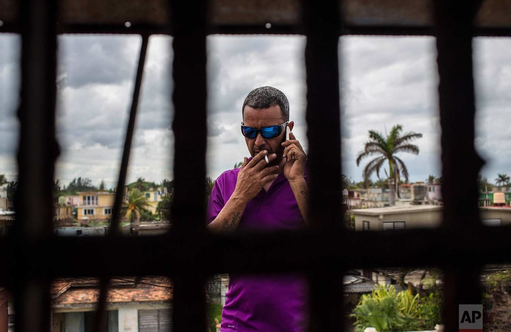 In this Saturday, Nov. 4, 2017 photo, pigeon breeder Ernesto Eng Lopez speaks on his cell, seen through one of his pigeon cages on his roof in Havana, Cuba. (AP Photo/Desmond Boylan)