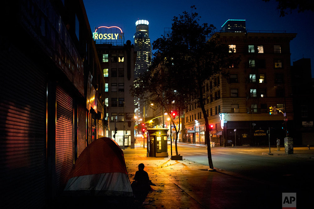 Sitting in front of a tent pitched on a sidewalk, Daniel Shawn, a 48-year-old homeless man, is silhouetted against the street lights Wednesday, Sept. 6, 2017, in downtown Los Angeles. Since last fall, Los Angeles city and county voters approved spending $4.7 billion in an attempt to tackle the problem, largely through adding low-cost housing. (AP Photo/Jae C. Hong)