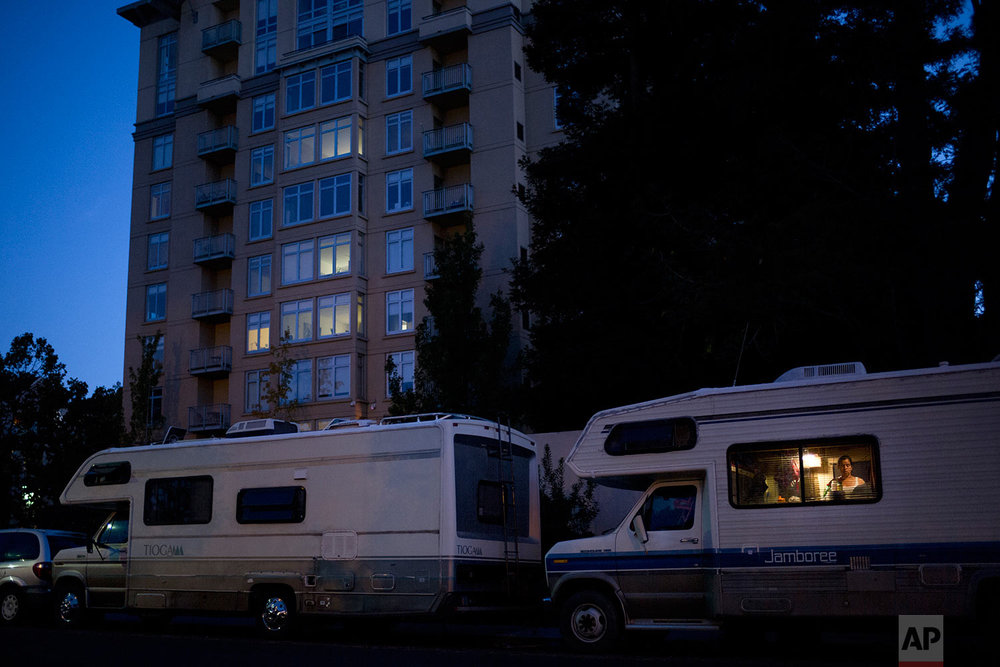 Delmi Ruiz, 41, who is five months pregnant, works in the kitchen area of her RV parked in front of an apartment building, where the monthly rent for a one-bedroom unit is more than $3000, Monday, Oct. 23, 2017, in Mountain View, Calif. Ruiz and her husband, who works as a landscaper earning minimum wage, have been living in the RV for more than two years with their four children after they could no longer afford the rent. (AP Photo/Jae C. Hong)