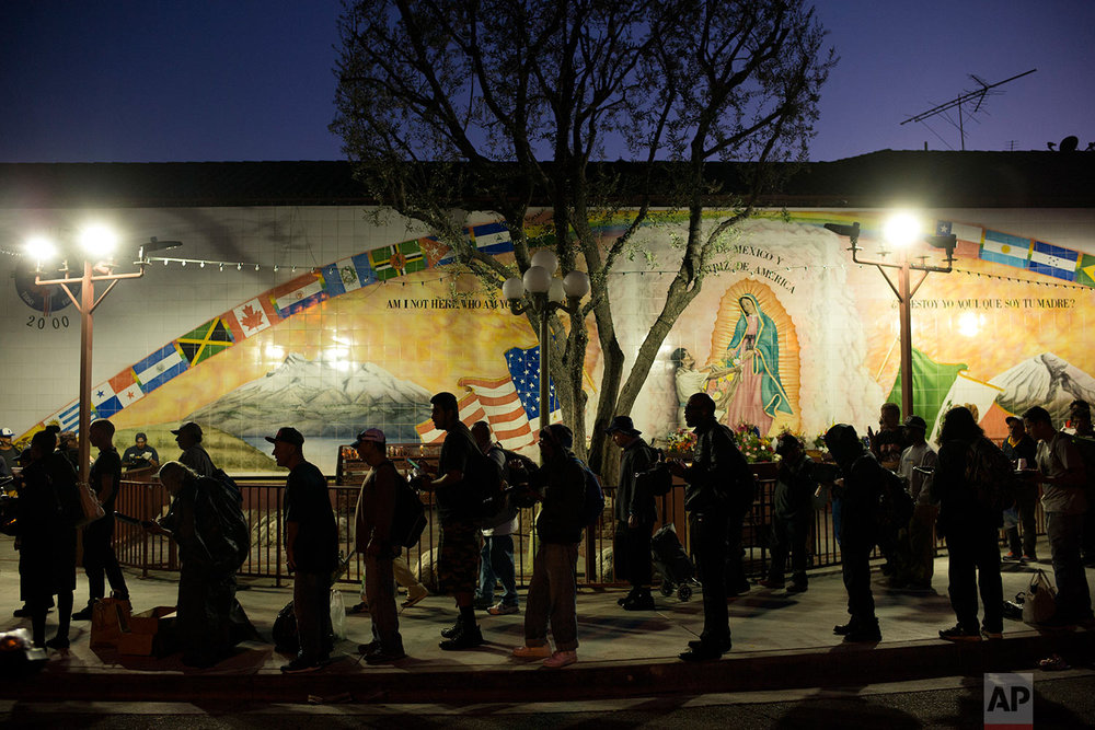 Homeless people wait in line for a meal served by a community organization outside Our Lady Queen of Angels Catholic Church Thursday, Sept. 21, 2017, in Los Angeles. A homeless crisis of unprecedented proportions is rocking the West Coast, and its victims are being left behind by the very things that mark the region's success: soaring housing costs, rock-bottom vacancy rates and a roaring economy that waits for no one. (AP Photo/Jae C. Hong)