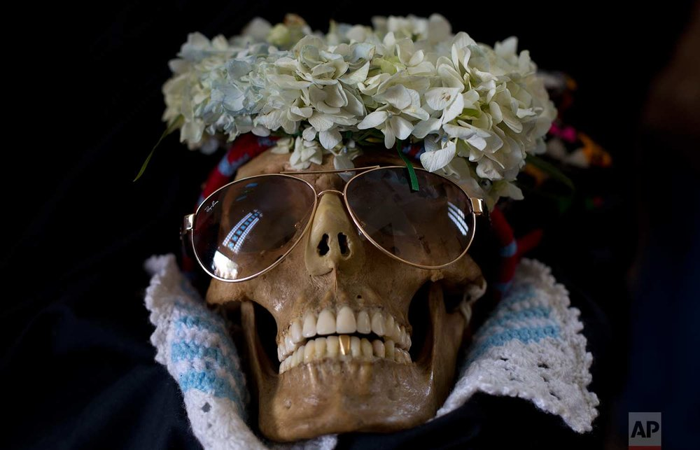 A human skull wearing sun glasses and flowers is displayed outside the General Cemetery chapel during the Natitas Festival in La Paz, Bolivia, Wednesday, Nov. 8, 2017. (AP Photo/Juan Karita)