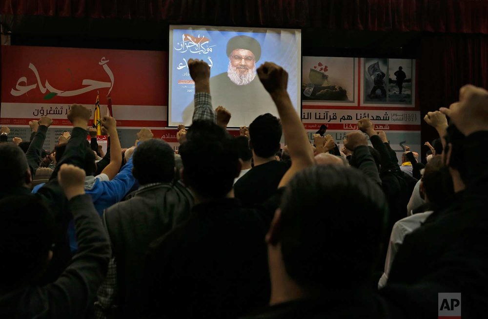 Hezbollah supporters raise their fists and cheer as they listen to a speech of Hezbollah leader Sheik Hassan Nasrallah, via a video link, during a rally marking Hezbollah Martyr's Day, in a southern suburb of Beirut, Lebanon, Friday, Nov. 10, 2017. (AP Photo/Bilal Hussein)