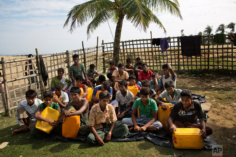 In this Nov. 4, 2017, photo, newly arrived Rohingya Muslims with yellow plastic drums they used to aid flotation while crossing the Naf river wait in Shah Porir Dwip to be transferred to a refugee camp in Cox's Bazar, Bangladesh.  (AP Photo/Bernat Armangue)