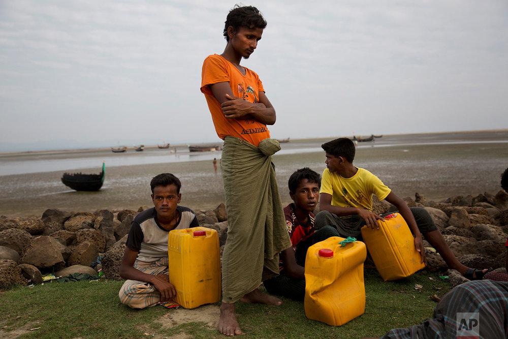 In this Nov. 5, 2017, photo, newly arrived Rohingya Muslim Aman Ullah, 18, left, Abdul Karim, 19, second left, Mohammed Sadek, 14, third left and Robiul Hassan, 15, right, wait in Shah Porir Dwip, Bangladesh to be transferred to a refugee camp in Cox's Bazar, Bangladesh.(AP Photo/Bernat Armangue)