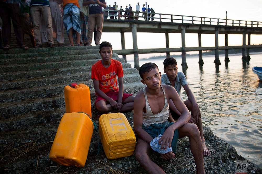 In this Nov. 4, 2017, photo, from left to right: Rohingya Muslims Belal Hussain, 15; Kamal Hussain, 18; and Robiul Hassan, 15; rest after swimming the Naf river in Shah Porir Dwip, Bangladesh. The yellow plastic drums in picture were used as a flotation aid. (AP Photo/Bernat Armangue)