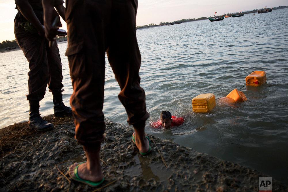 In this Nov. 4, 2017, photo, Rohingya Muslim Belal Hussain, 15, center, arrives at Shah Porir Dwip, Bangladesh, after swimming Naf river. The Naf river is a natural border between Myanmar and Bangladesh. (AP Photo/Bernat Armangue)
