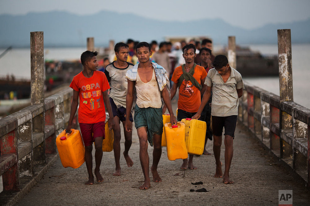 In this Nov. 4, 2017, photo, Rohingya Muslims carrying yellow plastic drums they used as flotation devices walk down the Shah Porir Dwip dock after reaching Bangladesh. (AP Photo/Bernat Armangue)