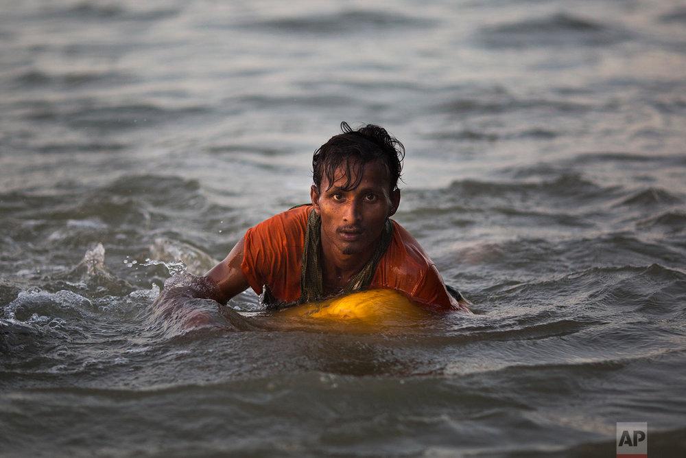In this Nov. 4, 2017, photo, Rohingya Muslim Abdul Karim, 19, uses a yellow plastic oil container as a flotation device as he swims the Naf river while crossing the Myanmar-Bangladesh border in Shah Porir Dwip, Bangladesh.(AP Photo/Bernat Armangue)