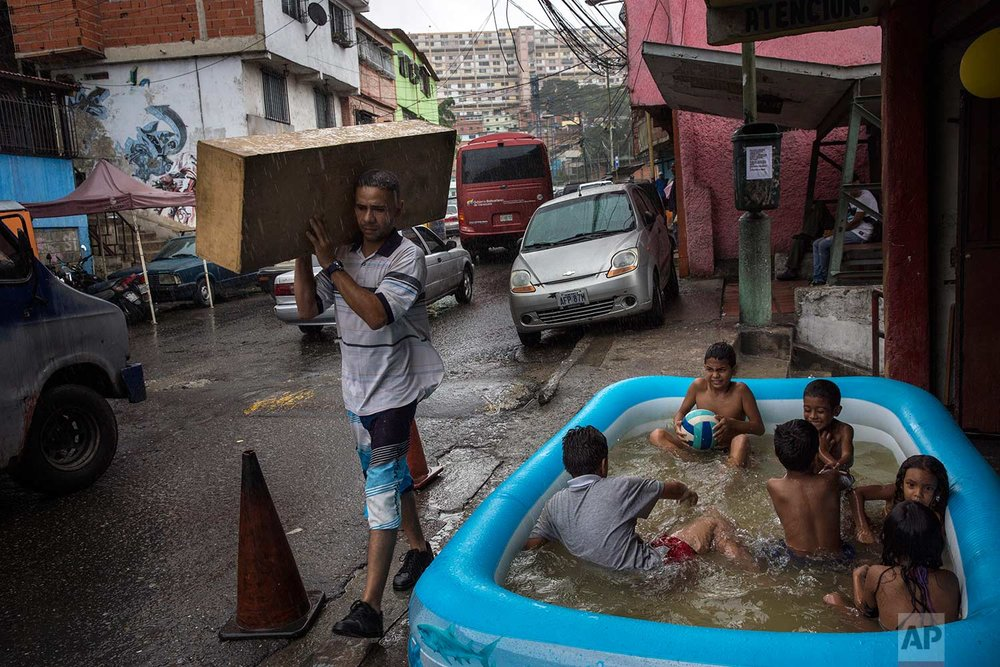 Children play in an inflatable swimming pool in the working class 23 de Enero neighborhood as it rains lightly in Caracas, Venezuela, Saturday, Oct. 21, 2017. (AP Photo/Rodrigo Abd)