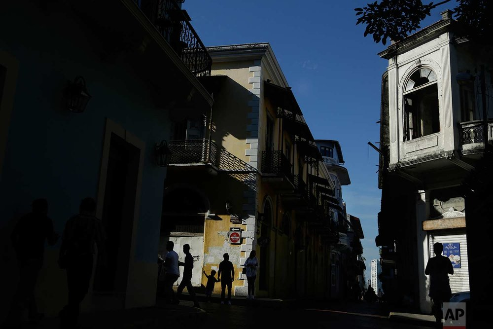People walk in a street of the Casco Viejo neighborhood in Panama City, Saturday, Oct. 7, 2017. (AP Photo/Arnulfo Franco)