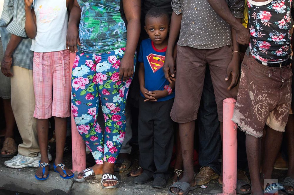 A boy wearing a Superman T-shirt stands with a group of grownups watching a ceremony marking the 211th anniversary of the assassination of independence hero Gen. Jean-Jacques Dessalines, in Port-au-Prince, Haiti, Tuesday Oct. 17, 2017. (AP Photo/Dieu Nalio Chery)