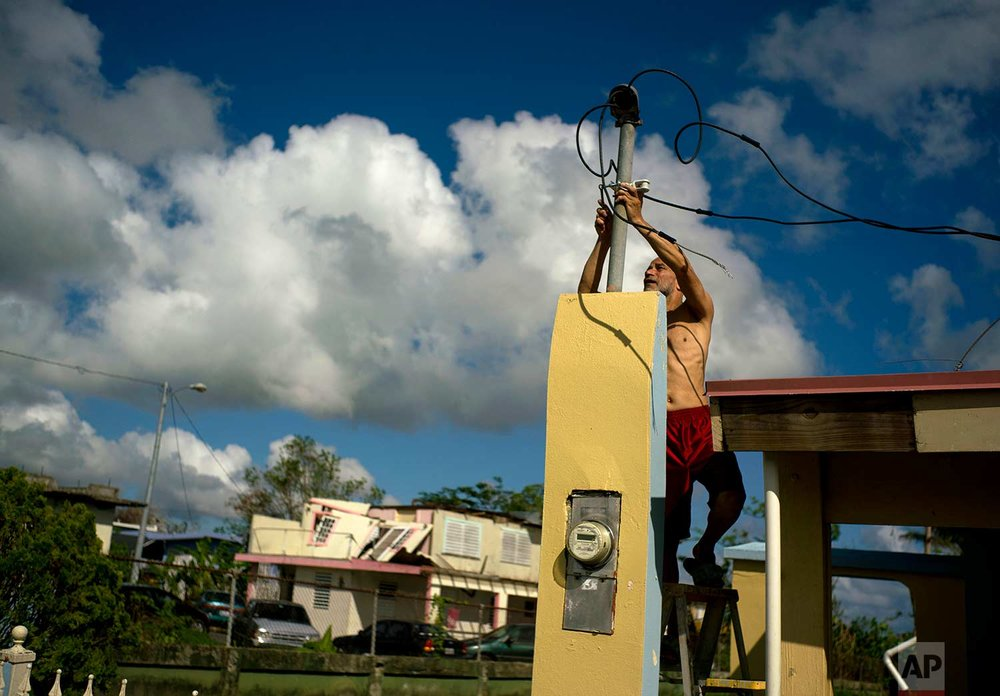 In this Friday, Oct. 13, 2017 photo, a resident tries to connect electrical lines downed by Hurricane Maria in preparation for when electricity is restored in Toa Baja, Puerto Rico. (AP Photo/Ramon Espinosa)