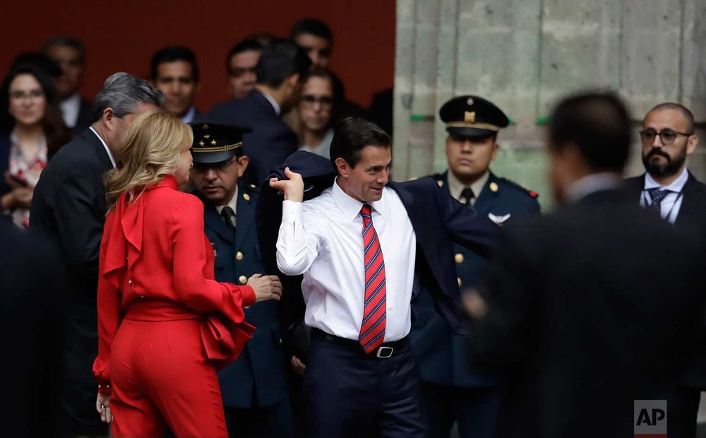 Mexican President Enrique Pena Nieto puts on his jacket as his wife Angelica Rivera looks on before welcoming Canadian Prime Minister Justin Trudeau and his wife Sophie Gregoire Trudeau to the National Palace in Mexico City, Thursday, Oct. 12, 2017.  (AP Photo/Rebecca Blackwell)