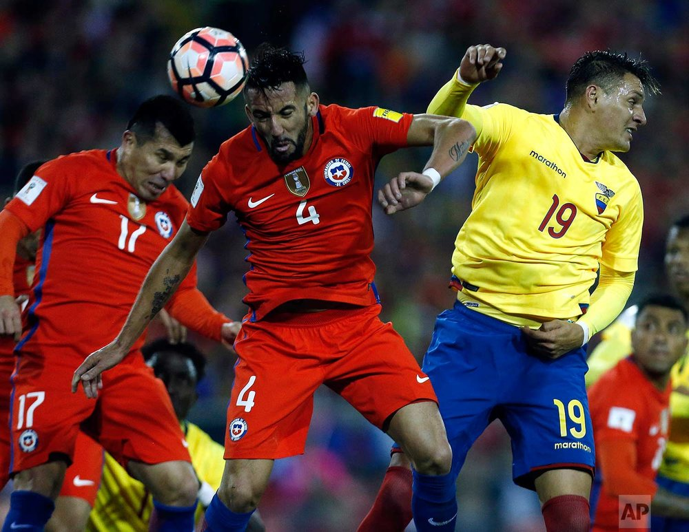 Chile's Mauricio Isla, center, fights to head the ball against Ecuador's Joao Plata Cotera, right, during a 2018 World Cup qualifying soccer match in Santiago, Chile, Thursday, Oct. 5, 2017. (AP Photo/Luis Hidalgo)