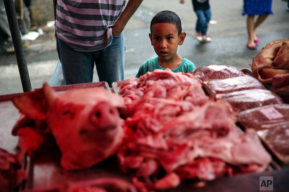A boy looks at a butcher's stand at a street market downtown in Caracas, Venezuela, Saturday, Oct. 21, 2017. (AP Photo/Rodrigo Abd)