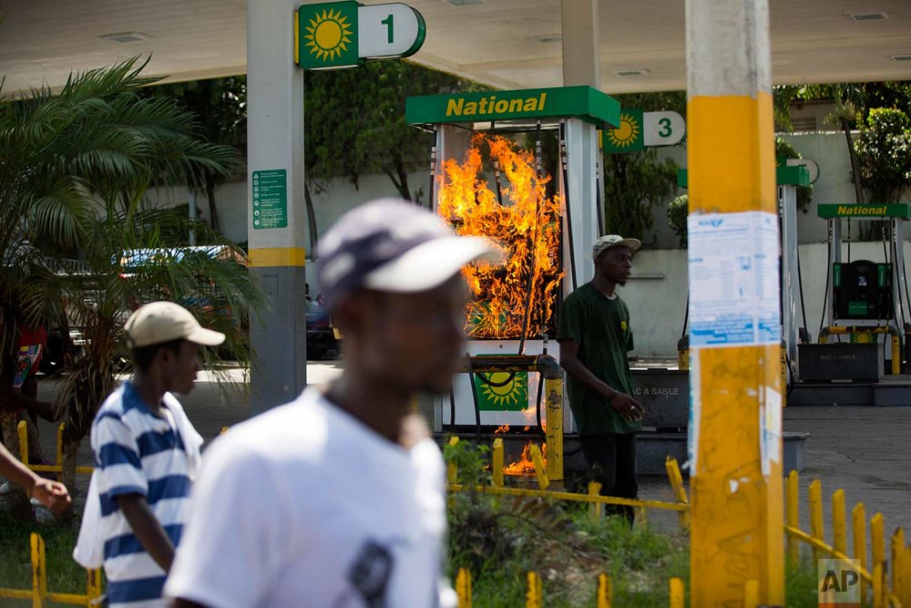 A gas pump set on fire by protesters goes up in flames during a protest against government tax hikes in Port-au-Prince, Haiti, Tuesday, Oct. 17, 2017. (AP Photo/Dieu Nalio Chery)