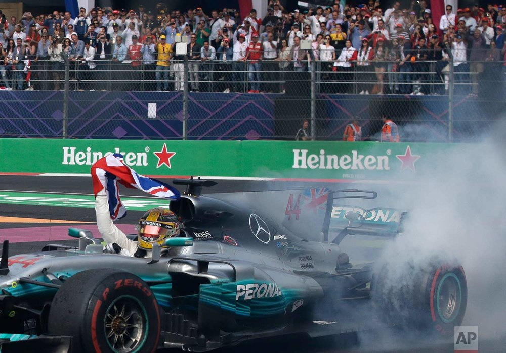 Mercedes driver Lewis Hamilton, of Britain, celebrates at the end of the Formula One Mexico Grand Prix auto race at the Hermanos Rodriguez racetrack in Mexico City, Sunday, Oct. 29, 2017. (AP Photo/Rebecca Blackwell)