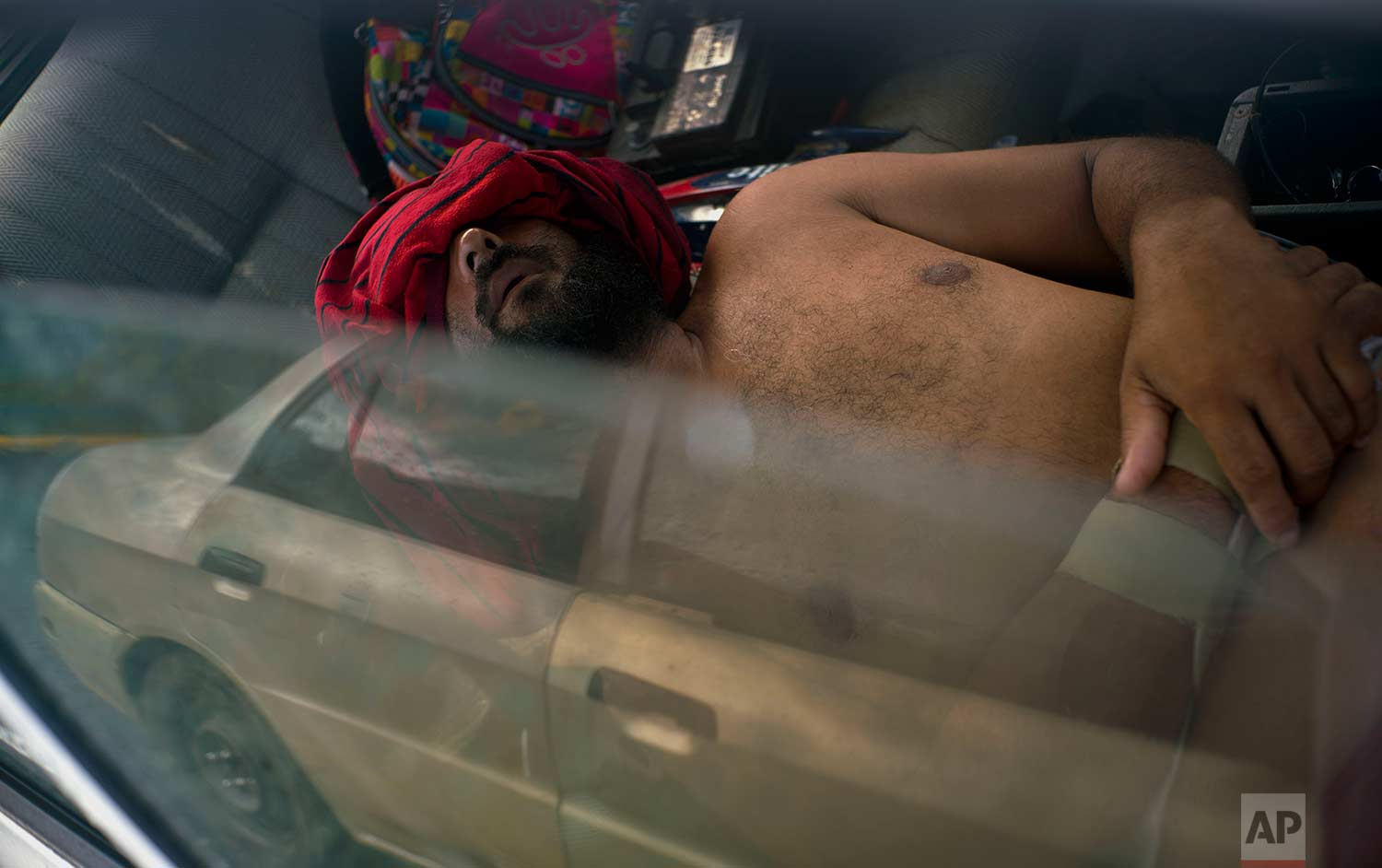 In this Saturday, Oct. 14, 2017 photo, Arturo de Jesus Melendez sleeps in his car with a shirt over his eyes, after he couldn't sleep in the school-turned-shelter due to the noise in Toa Baja, Puerto Rico. (AP Photo/Ramon Espinosa)