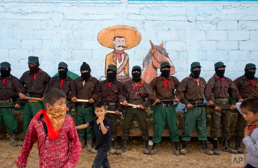 In this Monday, Oct. 16, 2017 photo, members of the Zapatista National Liberation Army (EZLN) provide security for a campaign rally by presidential candidate for the National Indigenous Congress, Maria de Jesus Patricio, in the Zapatista stronghold of La Garrucha in the southern state of Chiapas, Mexico. (AP Photo/Eduardo Verdugo)