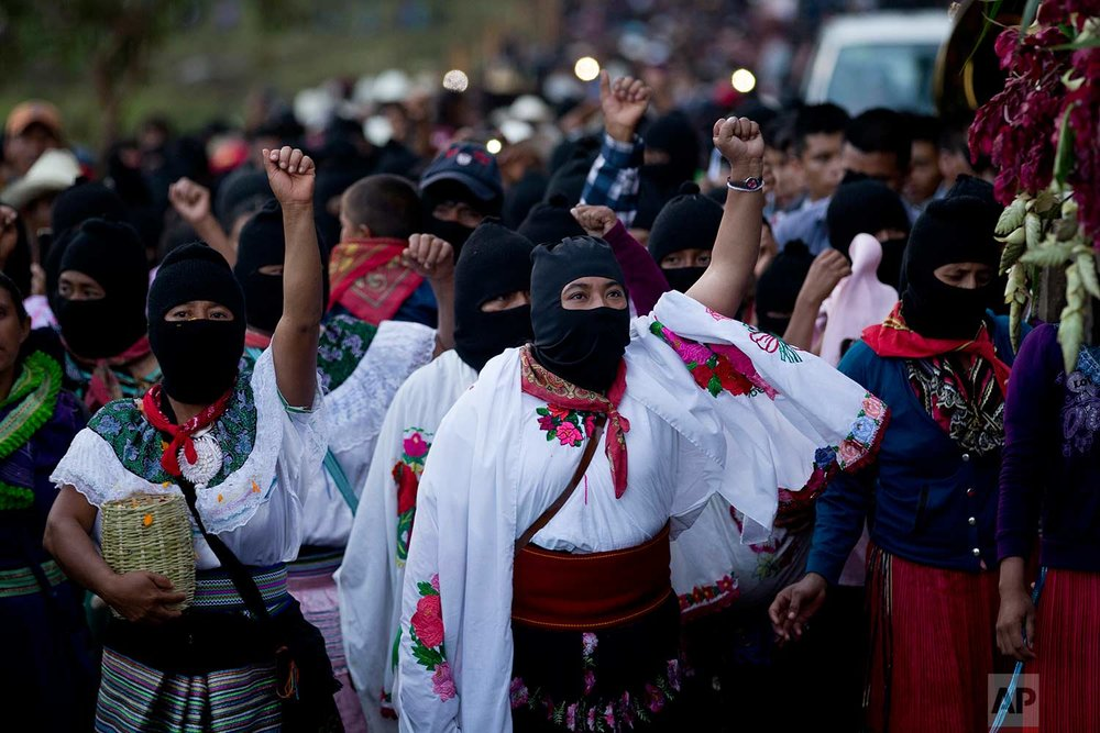 In this Sunday, Oct. 15, 2017 photo, masked indigenous women raise their fists to show support for Maria de Jesus Patricio, presidential candidate for the National Indigenous Congress, during a rally in the Zapatista stronghold of Morelia, in the southern state of Chiapas, Mexico. (AP Photo/Eduardo Verdugo)
