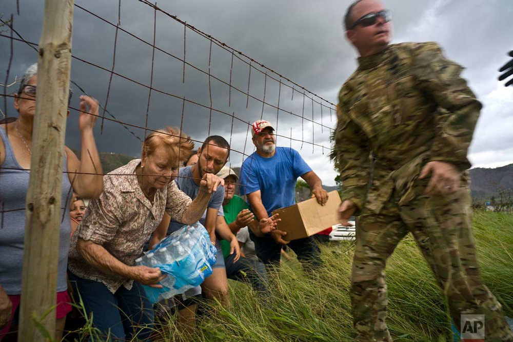 A member of the Puerto Rican National Guard delivers food and water brought via helicopter to victims of Hurricane Maria, to the  San Lorenzo neighborhood of Morovis, Puerto Rico, Saturday, Oct. 7, 2017. (AP Photo/Ramon Espinosa)