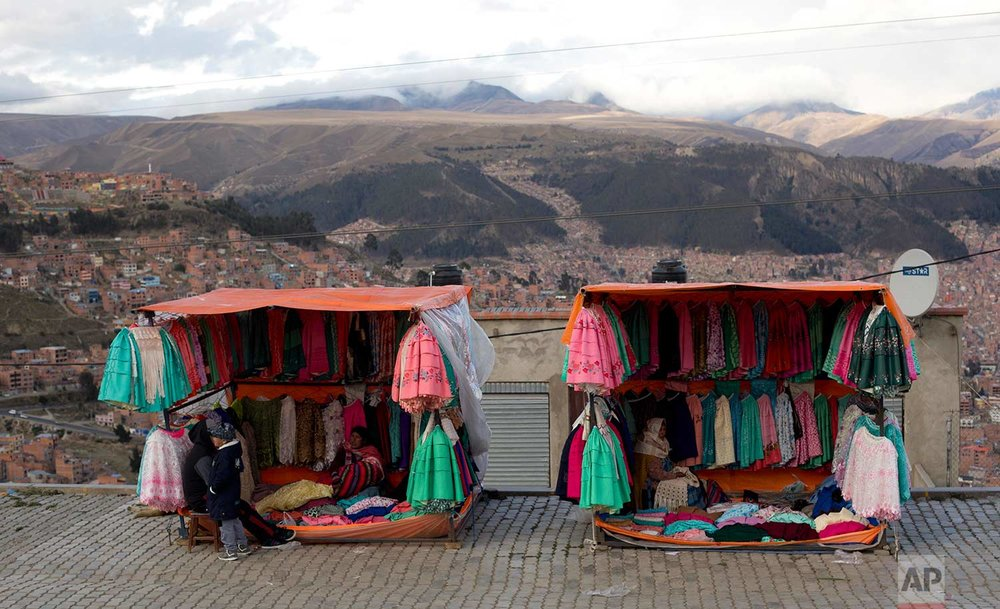 Traditional Andean women's skirts hang for sale at vendors' stores set up along the road between El Alto and La Paz, Bolivia, Thursday, Oct. 12, 2017. (AP Photo/Juan Karita)