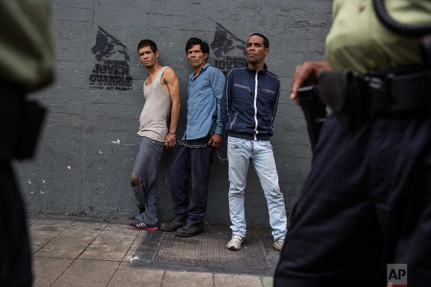 Suspected thieves chained together look at police after they were detained in downtown in Caracas, Venezuela, Wednesday, Oct. 25, 2017. (AP Photo/Rodrigo Abd)