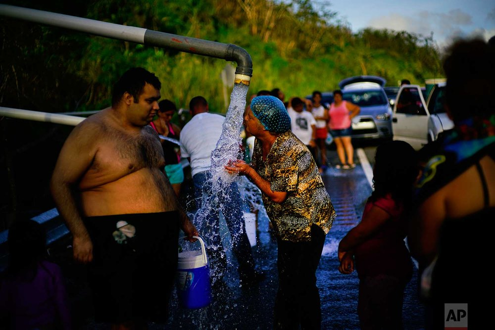 People who lost access to water in the wake of Hurricane Maria gather at pipes carrying water from a mountain creek, on the side of the road in Utuado, Puerto Rico, Saturday, Oct. 14, 2017. (AP Photo/Ramon Espinosa)