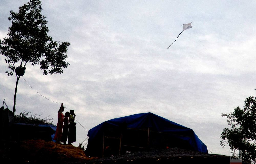 Rohingya Muslim children play with a kite at the Balukhali refugee camp in Ukhiya, Bangladesh, Wednesday, Nov. 15, 2017. (AP Photo/A.M. Ahad)
